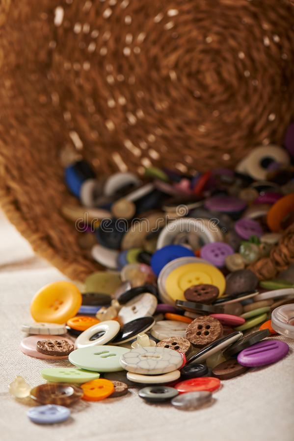 Cesta girada com os botões coloridos saídos da variedade, costurando acessórios fotografia de stock royalty free