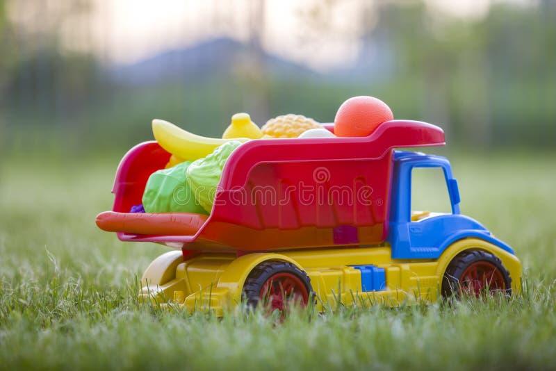 Cesta levando do caminhão colorido plástico brilhante do carro do brinquedo com frutas e legumes do brinquedo fora no dia de verã fotografia de stock royalty free