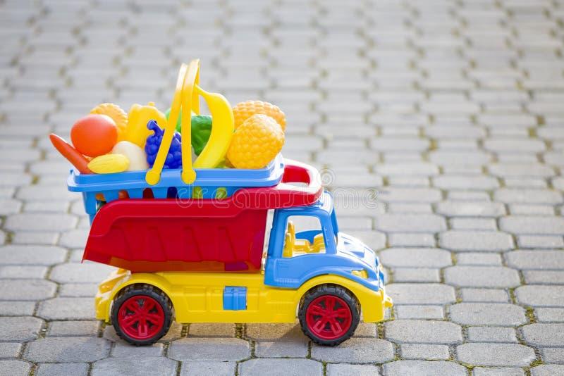 Cesta levando do caminhão colorido plástico brilhante do carro do brinquedo com frutas e legumes do brinquedo fora no dia de verã imagens de stock royalty free