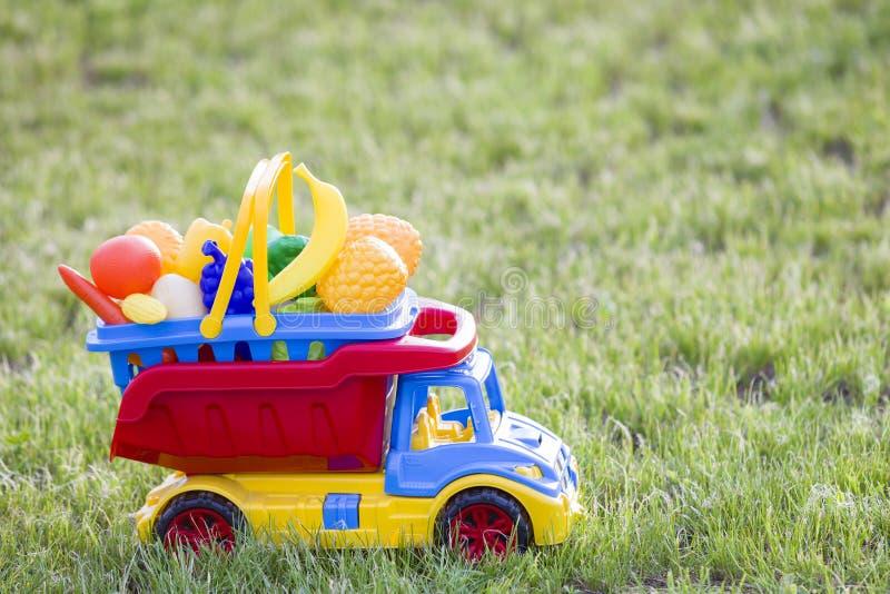 Cesta levando do caminhão colorido plástico brilhante do carro do brinquedo com frutas e legumes do brinquedo fora no dia de verã fotos de stock royalty free