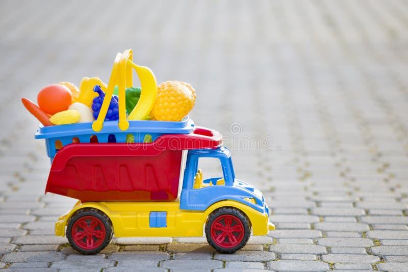 Cesta levando do caminhão colorido plástico brilhante do carro do brinquedo com frutas e legumes do brinquedo fora no dia de verã imagem de stock royalty free