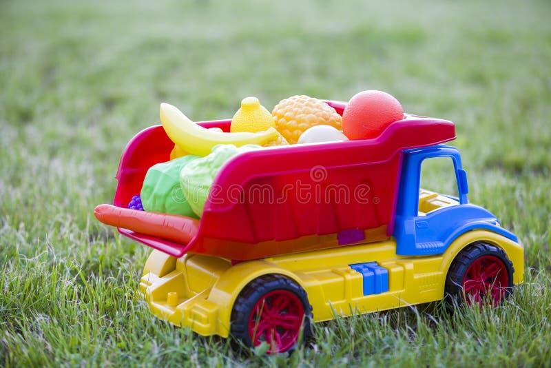 Cesta levando do caminhão colorido plástico brilhante do carro do brinquedo com frutas e legumes do brinquedo fora no dia de verã fotografia de stock