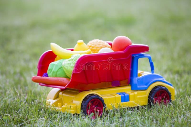 Cesta levando do caminhão colorido plástico brilhante do carro do brinquedo com frutas e legumes do brinquedo fora no dia de verã fotos de stock