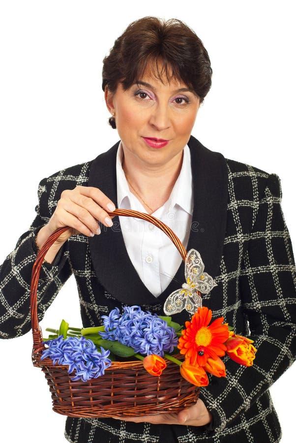 Cesta madura da terra arrendada da mulher com flores foto de stock