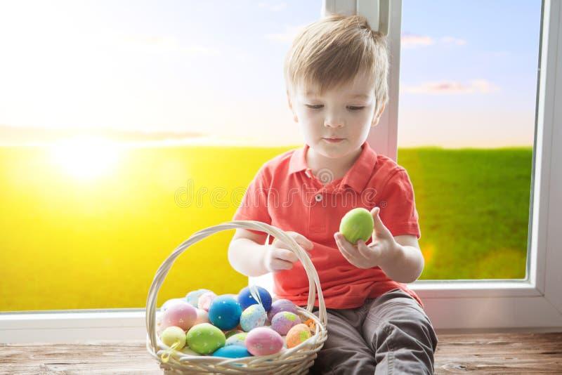 Cesta positiva de la tenencia del niño por completo de huevos de Pascua después de la caza del huevo que goza y que se sienta en  imagen de archivo libre de regalías