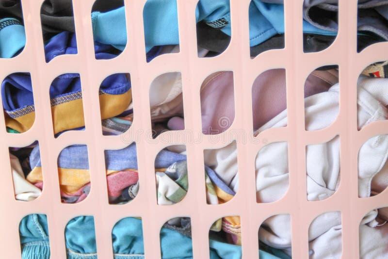 Cesta rosada con el lavadero sucio en piso foto de archivo