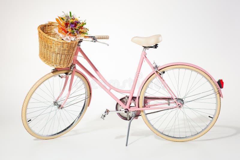 Cesta rosada de la flor del whith de la bicicleta del vintage aislada en el backg blanco imagen de archivo