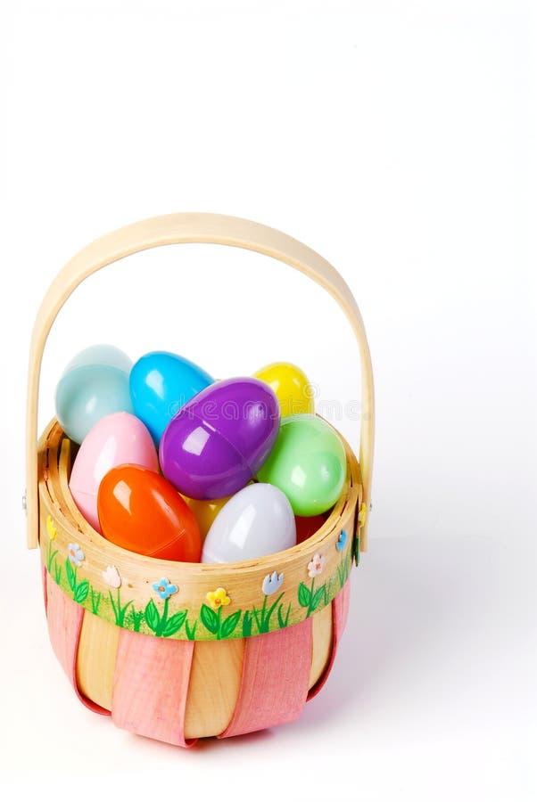 Cesta rosada de Pascua con los huevos coloridos foto de archivo libre de regalías