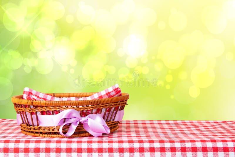 Cesta vazia com a fita roxa na toalha de mesa quadriculado vermelha com mola do sumário ou fundo amarelo brilhante do verão Para  imagem de stock