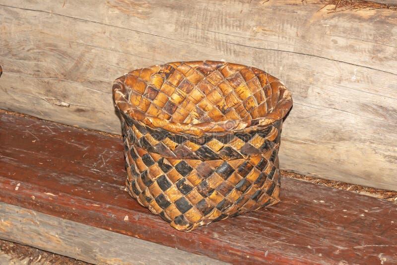 A cesta velha da casca de vidoeiro está em um banco de madeira imagens de stock royalty free