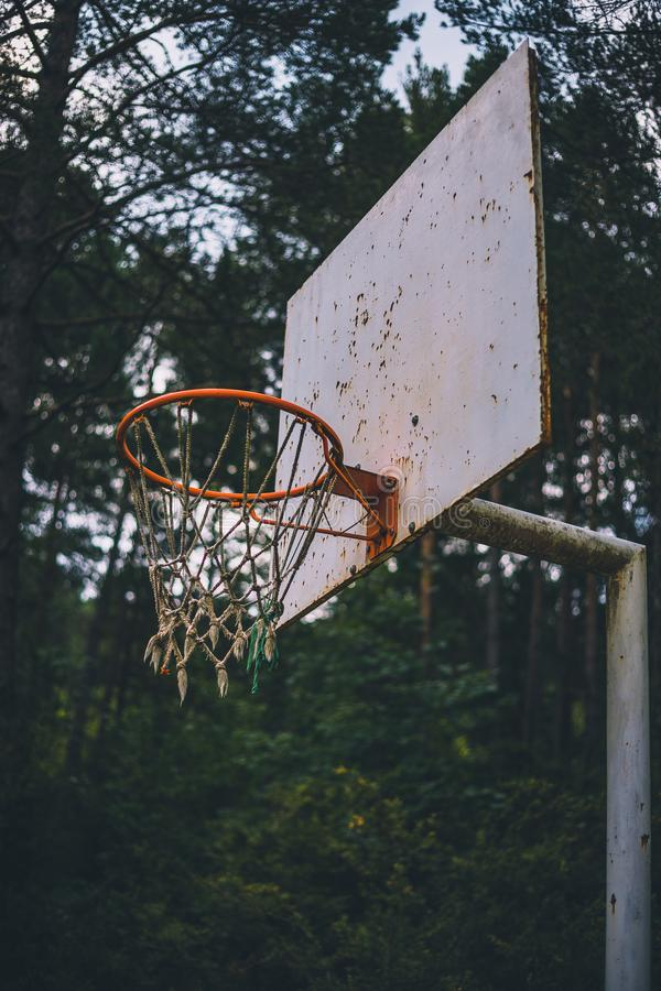 Cesta vieja y aherrumbrada del baloncesto en tiro bajo del campo del bosque imagen de archivo libre de regalías