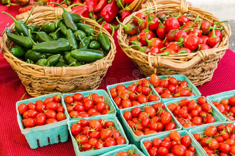 Cestas de pimientas y de tomates foto de archivo