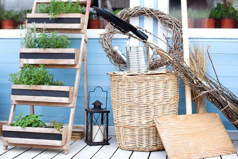 Cestas de vime ao lado do equipamento de jardim contra a parede de uma casa de campo azul F?rias sazonais do ver?o Plantas de jar foto de stock