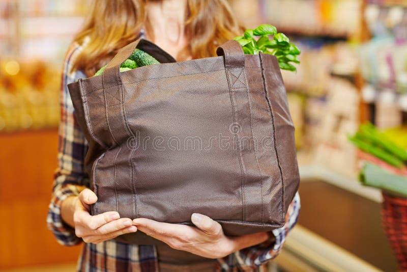 Cestino della spesa di trasporto della donna in pieno delle verdure fotografie stock libere da diritti