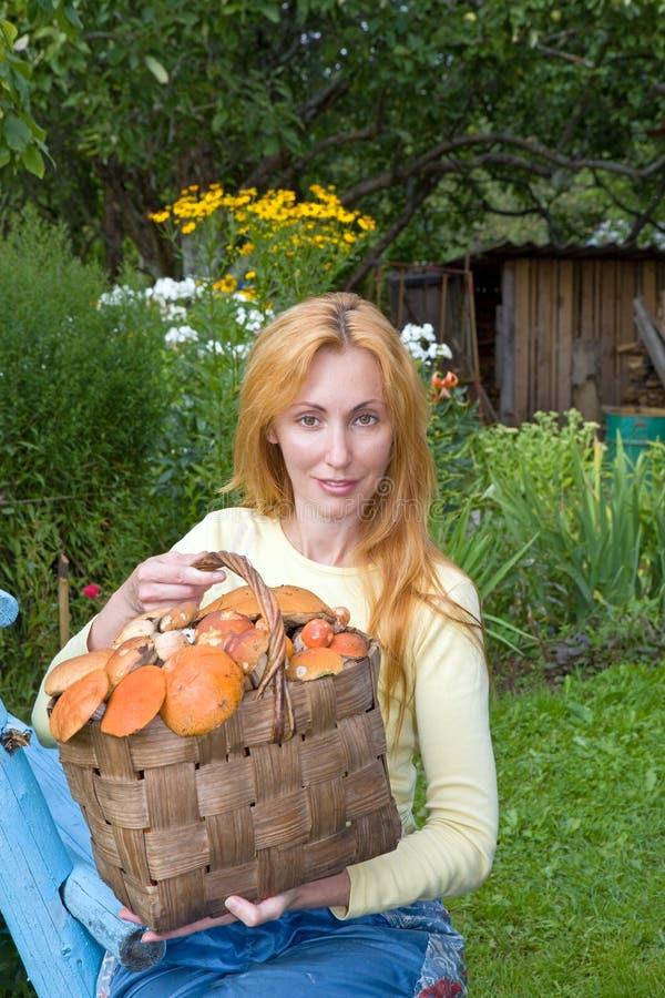 Cestino, funghi pieni e giovane donna-fungo P immagini stock libere da diritti