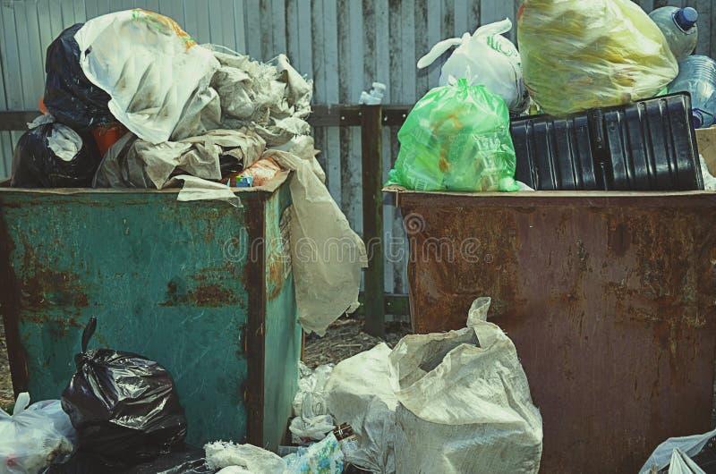 Cestino per i rifiuti in pieno di immondizia nel concetto della foresta del problema di ecologia fotografie stock