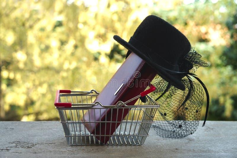 Cesto de compras com bolsa vermelha e o chapéu fêmea preto pequeno com véu e pena no estilo retro Carrinho de compras com present imagens de stock royalty free