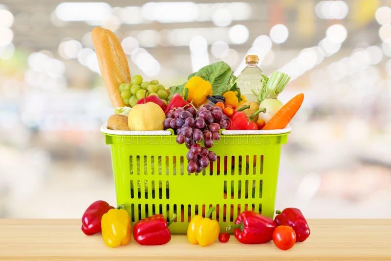 Cesto de compras enchido com as frutas e legumes na tabela de madeira imagens de stock