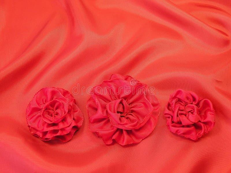 Cetim e flores vermelhos imagens de stock