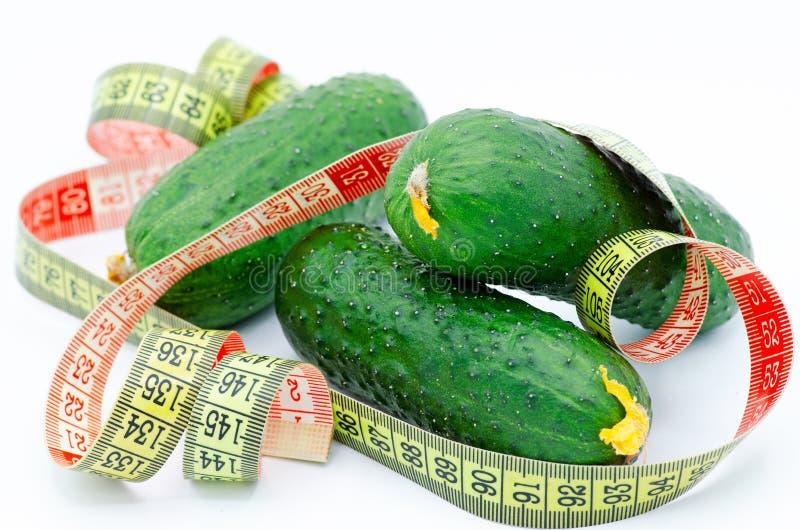 Cetrioli freschi verdi e nastro di misurazione su un fondo bianco, sul concetto di cibo sano e sul dimagramento fotografia stock libera da diritti