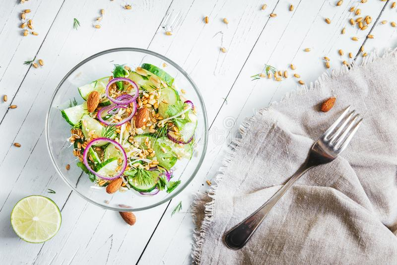 Cetrioli, insalata delle cipolle rosse con le mandorle e semi germinati di grano e dei germogli dei fagioli su una tavola di legn immagini stock