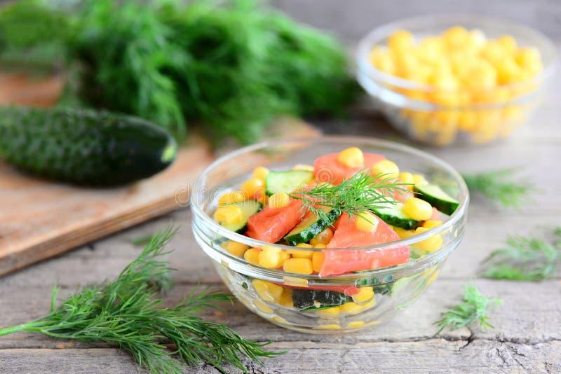 Cetrioli, pomodori e valerianella Insalata luminosa, colourful e squisita in una ciotola e sulla tavola di legno Insalata della v fotografia stock libera da diritti