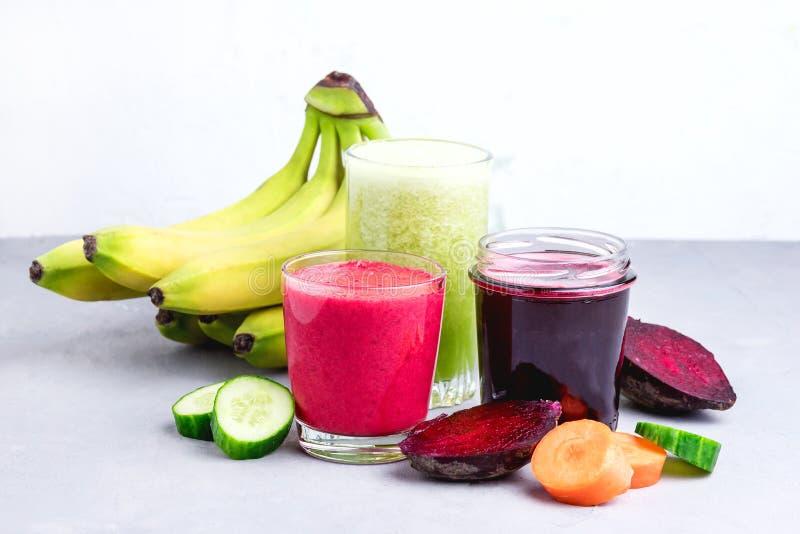 Cetriolo sano Juice Smoothie della banana della carota della barbabietola della disintossicazione in orizzontale onGray e bianco  fotografia stock