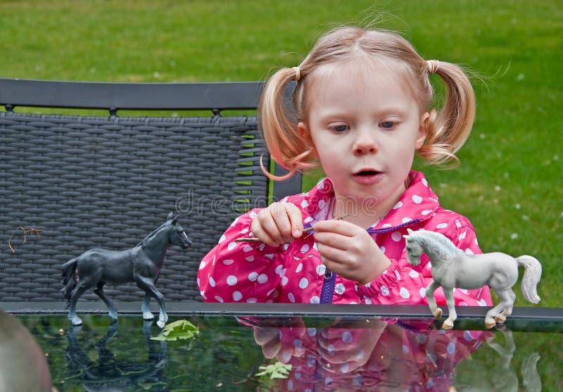 Petite fille jouant avec des chevaux de jouet photo libre de droits