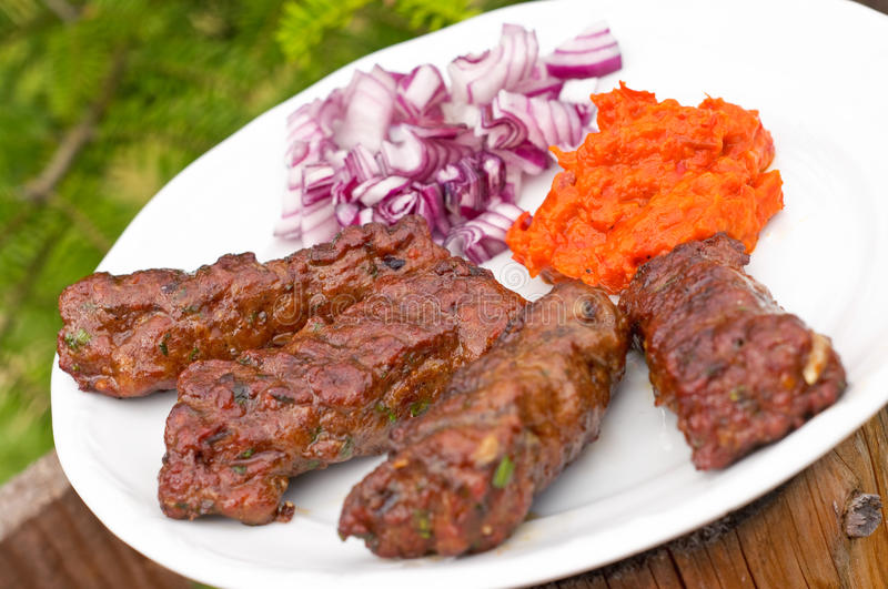 Cevapcici with ajvar paste. And red onion royalty free stock photo
