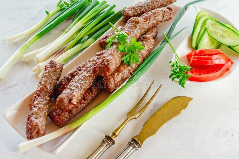 Cevapcici asado a la parrilla es un plato nacional balc?nico Cierre la fila de los kebabs fritos de la carne de vaca en un plato  imagen de archivo libre de regalías