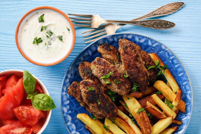 Cevapcici, balkanian grilled meat sausages with fries and yogurt dip. Cevapcici, balkanian grilled meat sausages with fries and yogurt dip stock photos