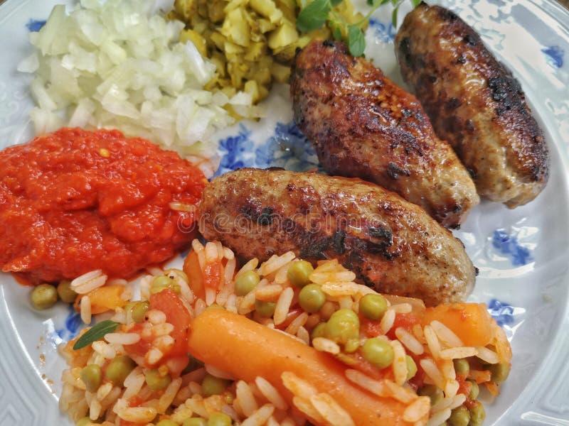 Cevapcici con ajvar, pepinos, cebollas y arroz de Djuvec, foto de archivo