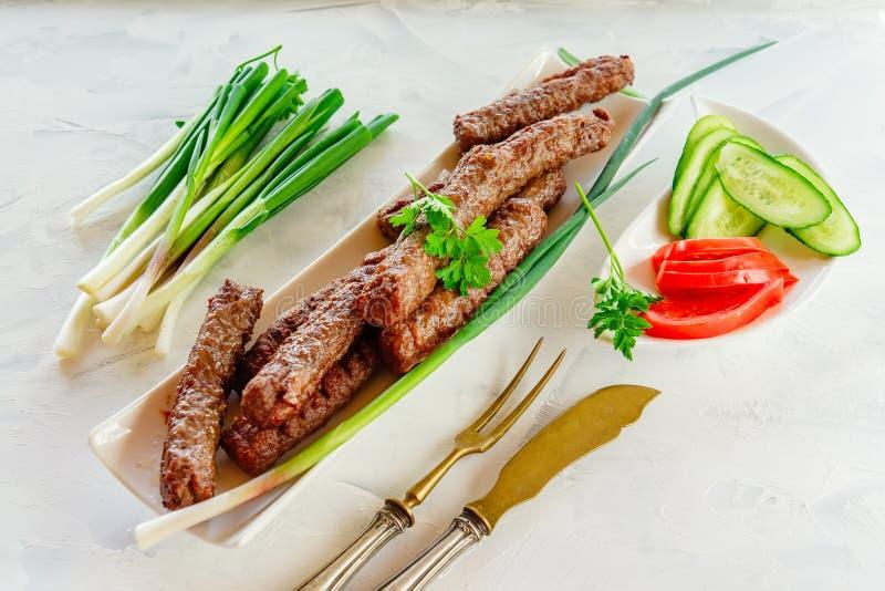Cevapcici grigliato ? un piatto nazionale del Balcani Chiuda la fila dei kebab fritti del manzo su un piatto rettangolare bianco  fotografia stock libera da diritti