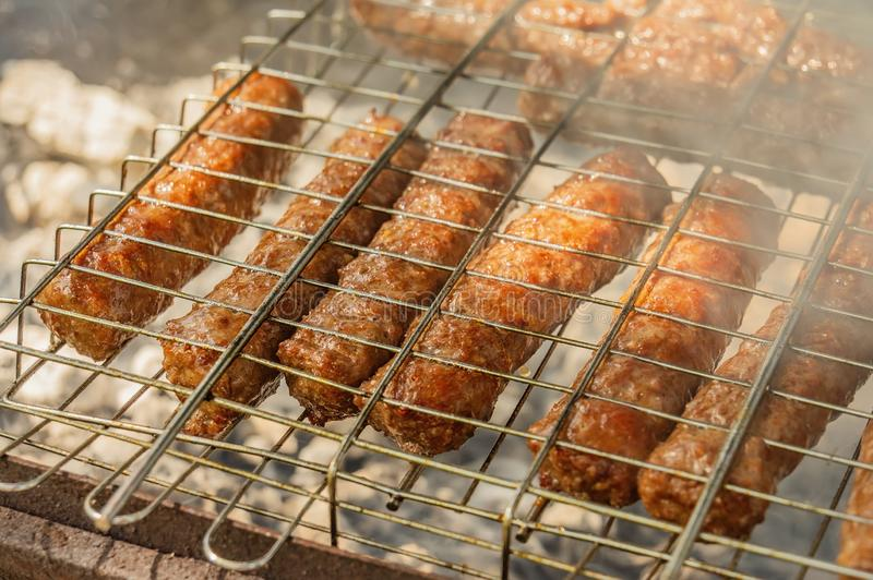Cevapcici on the grill are roasted on an open fire. Summer barbecue weekend. Shashlik is a national Caucasian dish. Close-up royalty free stock images