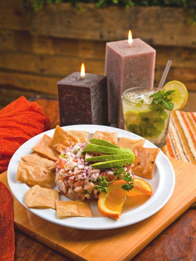 Ceviche dos peixes com abacate, microplaquetas de tortilha e um mojito fotografia de stock