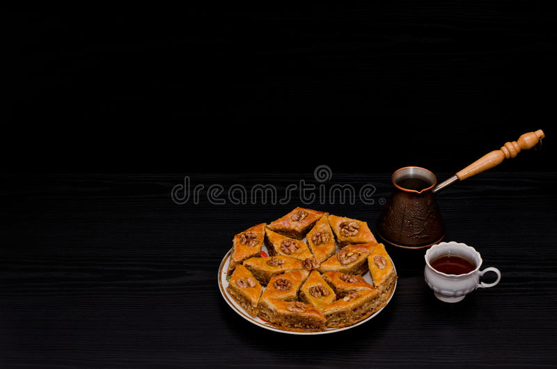 Cezve, coffee mug and a plate of traditional Turkish sweet baklava. Copy space, black background stock photography
