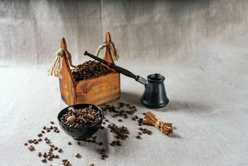 Cezve en geroosterde koffiebonen in vakje op een rustieke lijst, een kaneel en een droge citroen royalty-vrije stock foto