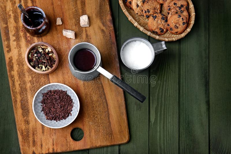 Cezve gorąca czekolada z składnikami i ciastkami na koloru drewnianym stole obrazy stock