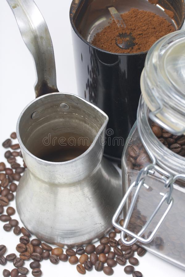 Cezve stand on a white surface. Next to a glass jar with coffee beans and a coffee grinder with ground coffee. royalty free stock photo