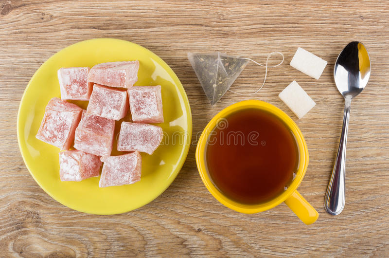 Chá, açúcar, saquinho de chá, pires amarelos com rakhat-lukum imagens de stock royalty free