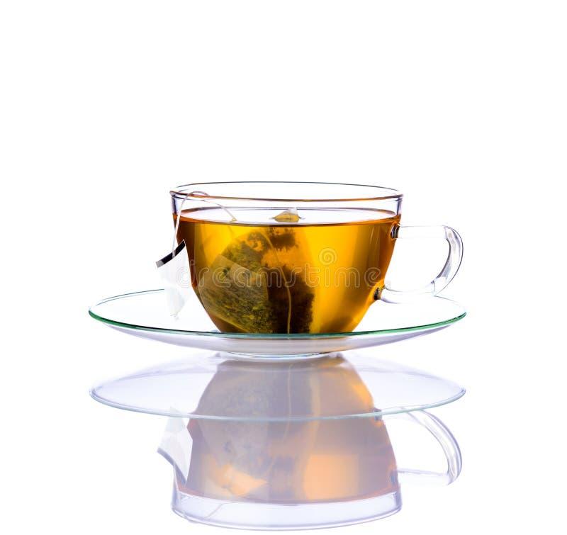 Chá amarelo com o saco no copo de vidro fotos de stock