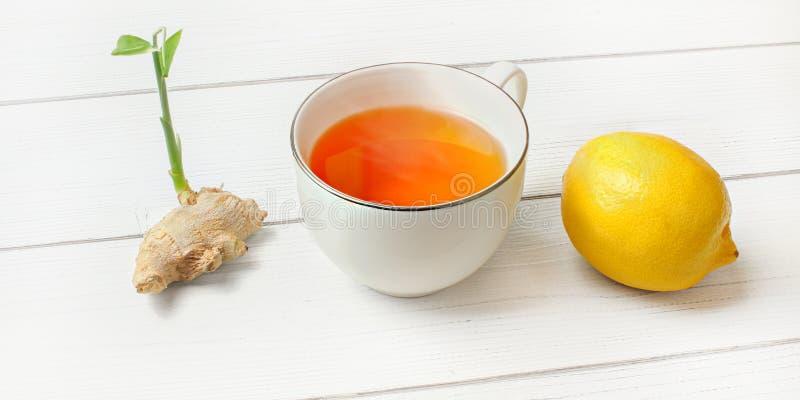 Chá ambarino quente no copo da porcelana, no limão inteiro e na raiz do gengibre com o broto verde ao lado dele nas placas branca fotografia de stock royalty free