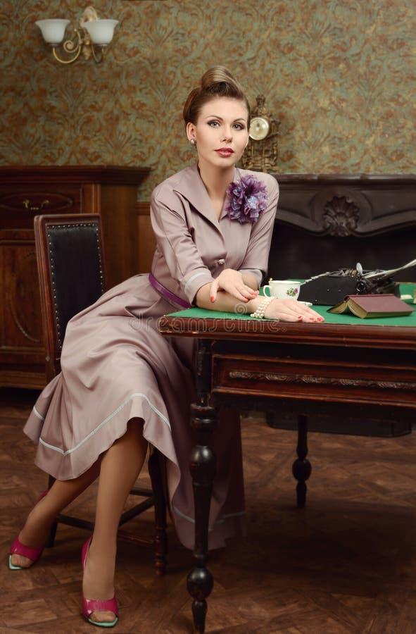 Chá bebendo da jovem mulher bonita de Pin Up no interior do vintage fotografia de stock