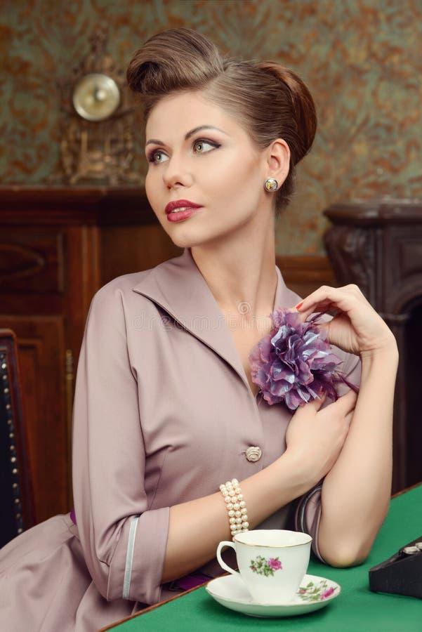 Chá bebendo da jovem mulher bonita de Pin Up no interior do vintage foto de stock royalty free