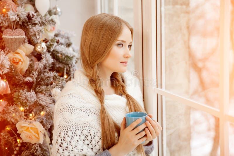 Chá bebendo da jovem mulher bonita na árvore de Natal Beauti imagem de stock royalty free