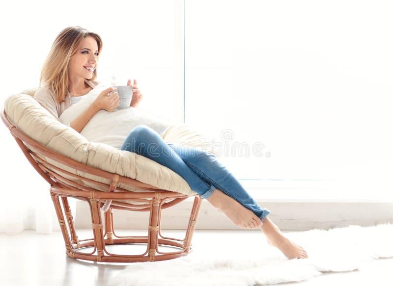 Chá bebendo da jovem mulher feliz ao sentar-se na poltrona foto de stock