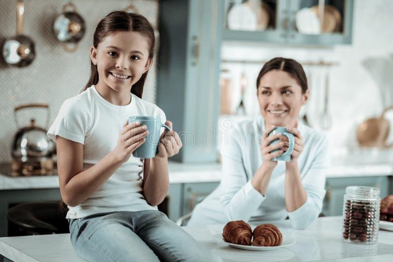 Chá bebendo da mãe e do daugther junto na cozinha fotos de stock royalty free