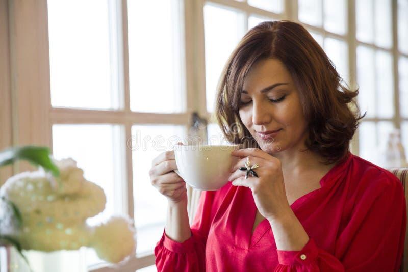 Chá bebendo da mulher bonita em uma tabela no restaurante acolhedor foto de stock