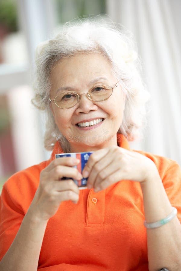 Chá bebendo da mulher chinesa sênior no sofá em casa fotografia de stock