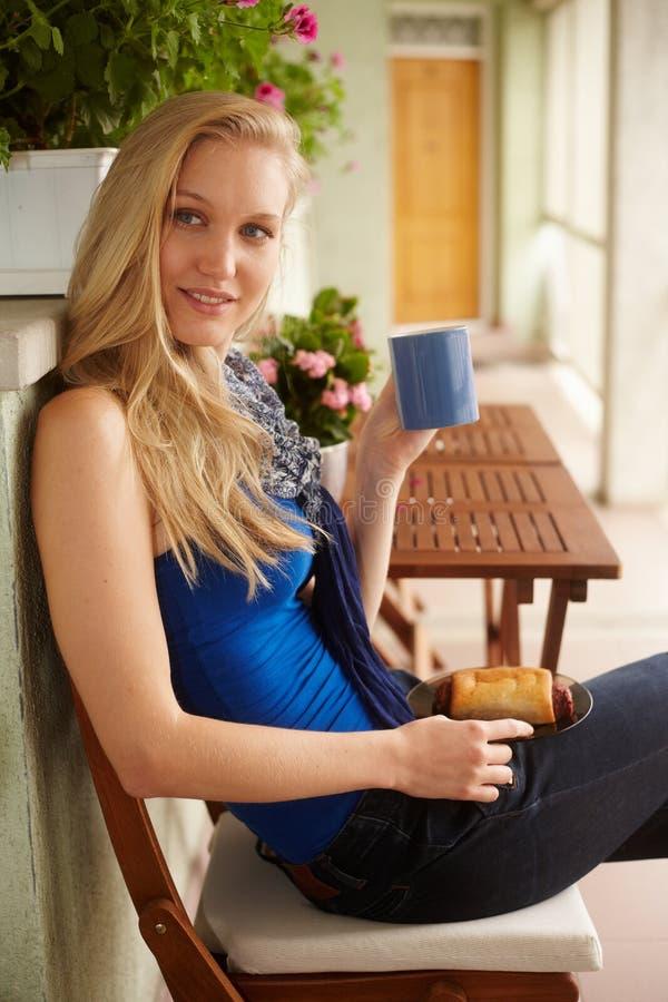 Chá bebendo da mulher loura nova no terraço fotos de stock
